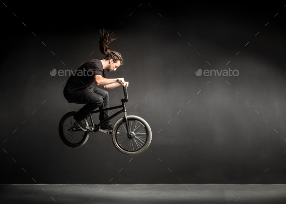 Young man doing a stunt on his BMX bicycle. - Stock Photo - Images