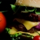 of Fresh Vegetables and Tasty Burger with Cheese and Beef Cutlets on the Black Background - VideoHive Item for Sale