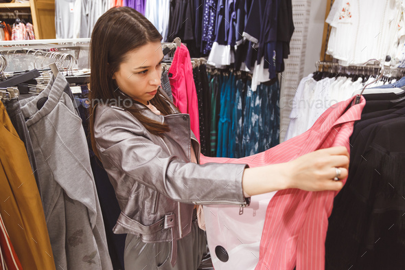 Young woman is buying a pink stripe suit. - Stock Photo - Images