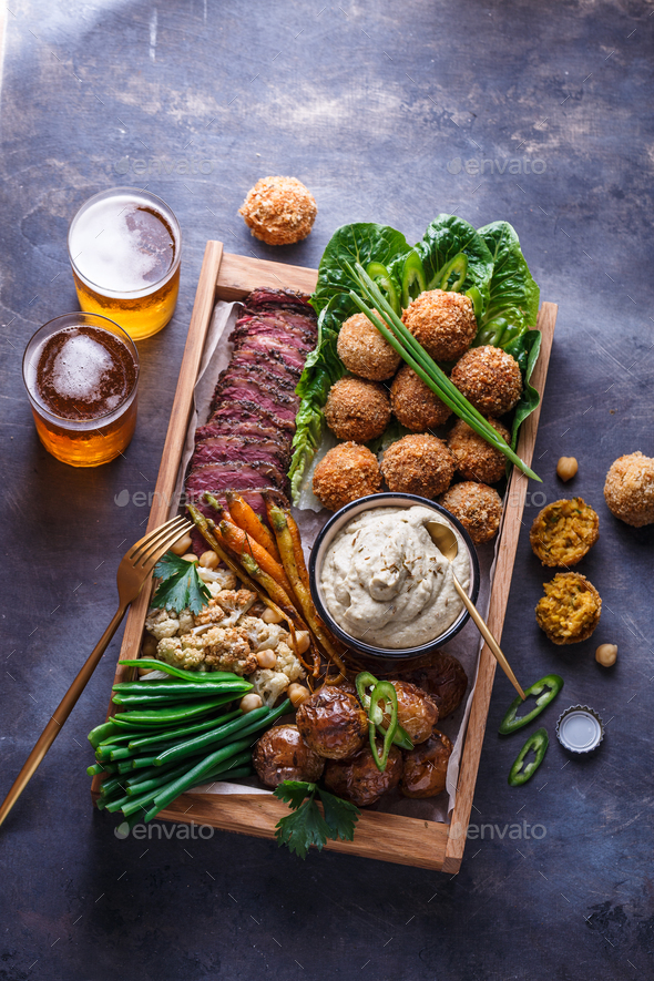 Pastrami, falafel, babagahanoush, veggies and beer in a wooden box, copyspace. - Stock Photo - Images