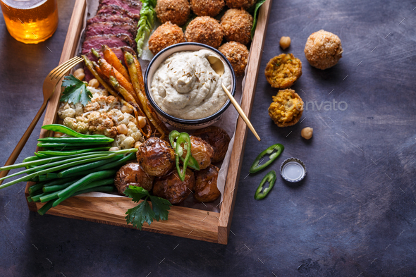 Close view of assorted meze appetizers beef, falafel, babaghanoush, potatoes in a box, copyspace. - Stock Photo - Images