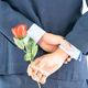 Businessman in suit holding red roses behind his back - PhotoDune Item for Sale