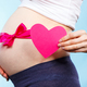 Pregnant woman holding heart and touching her belly with pink ribbon - PhotoDune Item for Sale