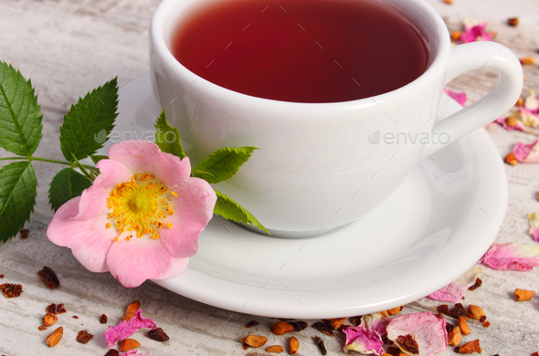 Cup of tea with wild rose flower on old rustic plank - Stock Photo - Images