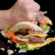 The Fist Smashes Burger Into Pieces. Black Mirror Surface - VideoHive Item for Sale