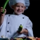 Merry Boy Wearing Chefs Suit Plays with Cucumbers at the Cooking Table. Black Background - VideoHive Item for Sale