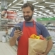 Smiling Supermarket Employee Using Mobile Phone and Holding Shopping Bag in Supermarket - VideoHive Item for Sale