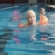 Little Girl in Inflatable Armlets Floats in the Pool - VideoHive Item for Sale
