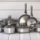 Set of stainless pots and pan with glass lids on the white woode - PhotoDune Item for Sale