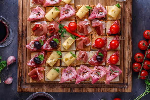 Close view of tiny bruschettas with prosciuto, ham and cheese - Stock Photo - Images