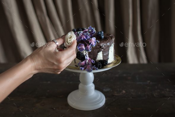 female hand pin rose in cake - Stock Photo - Images