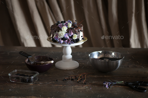 chocolate cake with flowers in dark interior - Stock Photo - Images