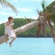 Adorable Little Girl at Tropical Beach Sitting on Palm Tree During Summer Vacation - VideoHive Item for Sale