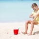 Little Girl with Bottle of Sun Cream Sitting at Tropical Beach - VideoHive Item for Sale