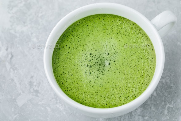 Japanese matcha green tea latte in white cup on gray background - Stock Photo - Images