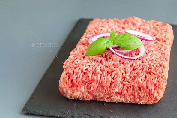 Minced meat from pork and beef, ground meat on dark slate board, - Stock Photo - Images