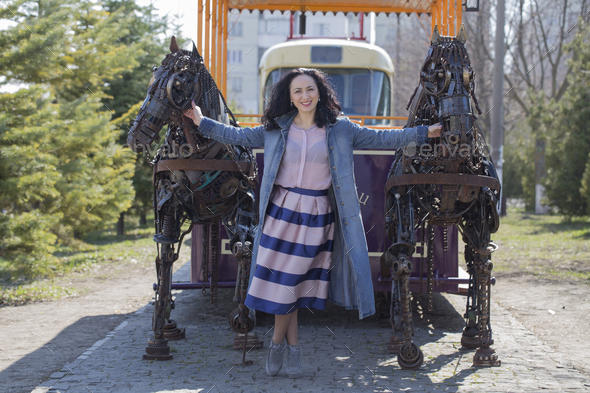 Lady standing between two metal horses - Stock Photo - Images