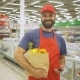 Handsome Delivery Man in Red Uniform with Paper Bag Standing in Supermarket - VideoHive Item for Sale