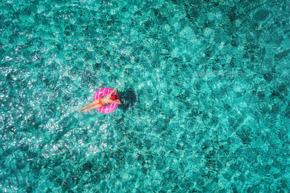 Aerial view of woman on the swim ring in the sea - Stock Photo - Images