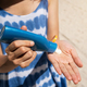 Young woman applying sunscreen on her hand at the tropical beach - PhotoDune Item for Sale