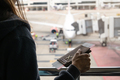 Young woman traveler with luggage holding passport looking at the airplan - PhotoDune Item for Sale