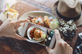 Young woman taking photo of food with smart phone in restaurant - PhotoDune Item for Sale