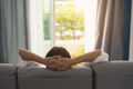 Young woman relaxing on sofa at cozy home and looking outside in living room - PhotoDune Item for Sale