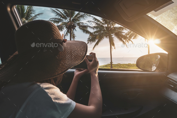 Young woman traveler looking and taking a photo beautiful sunset at the beach inside car - Stock Photo - Images