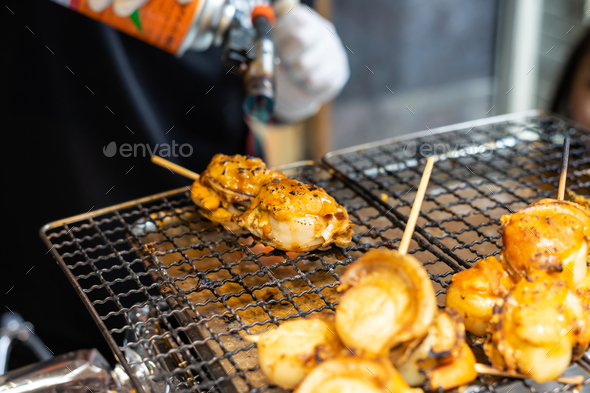 Chef using flame torch burn on Japanese scallop and Japanese shellfish - Stock Photo - Images