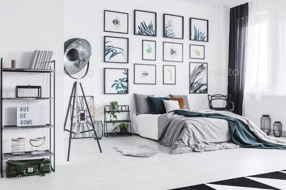 Real photo of a cozy bed standing next to a black lamp in a mono - Stock Photo - Images