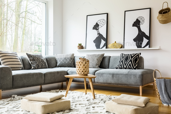 Poufs on carpet in bright african living room interior with grey Stock Photo by bialasiewicz