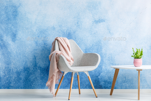 Single armchair with pastel blanket standing next to a coffee ta - Stock Photo - Images