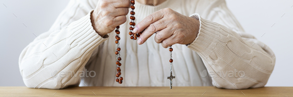 Close-up of religious senior person praying with rosary with cro - Stock Photo - Images