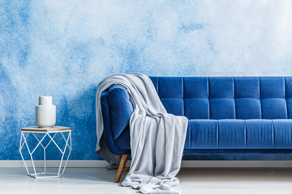 Navy blue sofa with gray blanket and openwork metal side table w - Stock Photo - Images