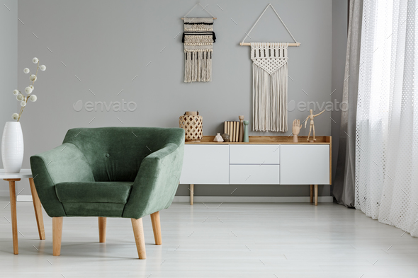 Real photo of a green armchair standing in a bright living room - Stock Photo - Images