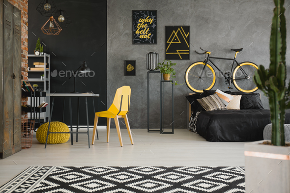 Black and yellow posters on concrete wall in spacious flat inter - Stock Photo - Images