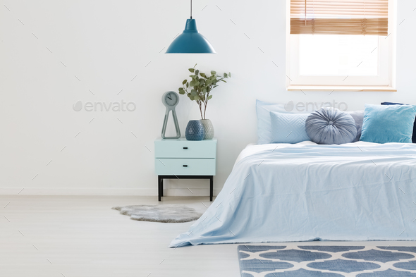 Real photo of a blue and white bedroom interior with wooden nigh - Stock Photo - Images