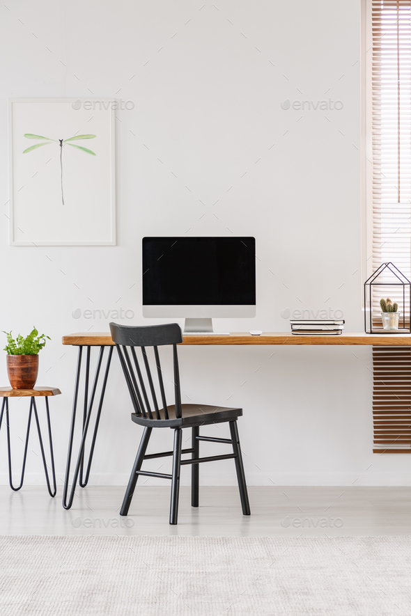 Simple interior of a home office with black chair standing at a - Stock Photo - Images