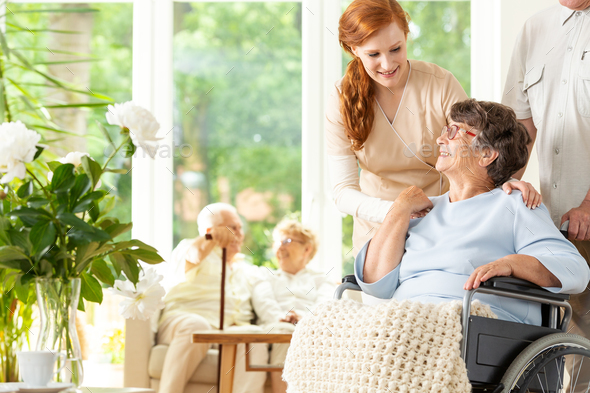 Tender caregiver saying goodbye to an elderly pensioner in a whe - Stock Photo - Images