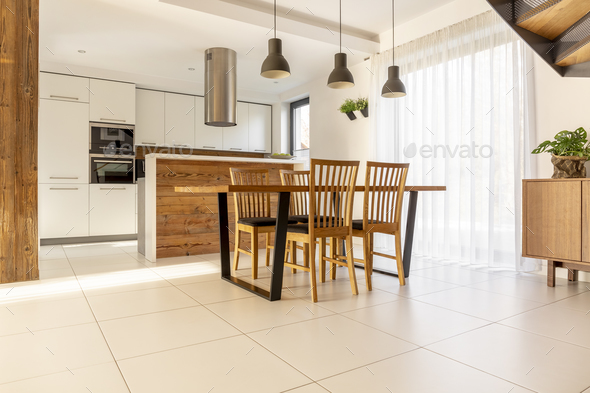Spacious, open kitchen and dining room with wooden table and cha - Stock Photo - Images