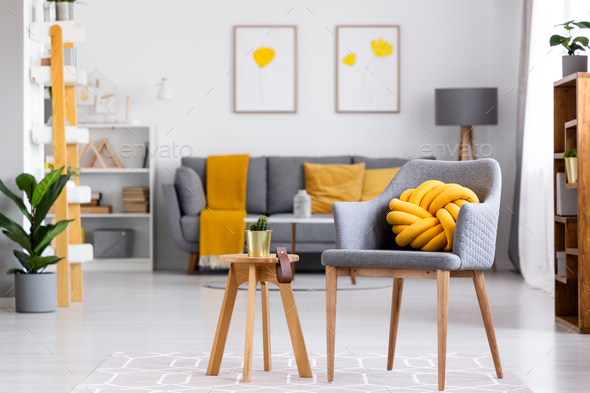 Yellow knot cushion on a gray armchair standing next to a wooden - Stock Photo - Images