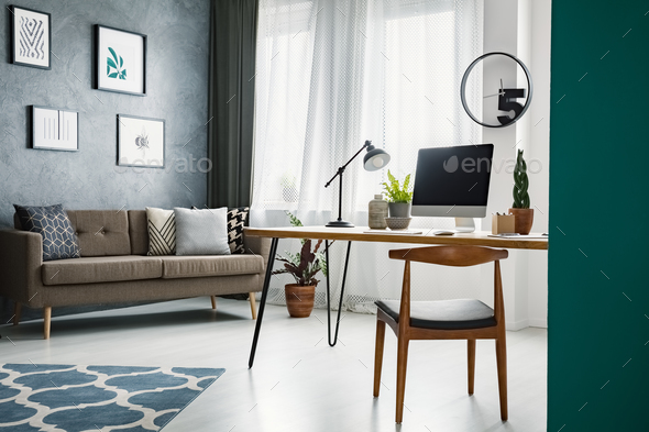 Wooden chair at desk in living room interior with work area and - Stock Photo - Images