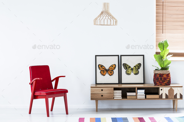 Red armchair next to a wooden cupboard with butterfly poster in - Stock Photo - Images