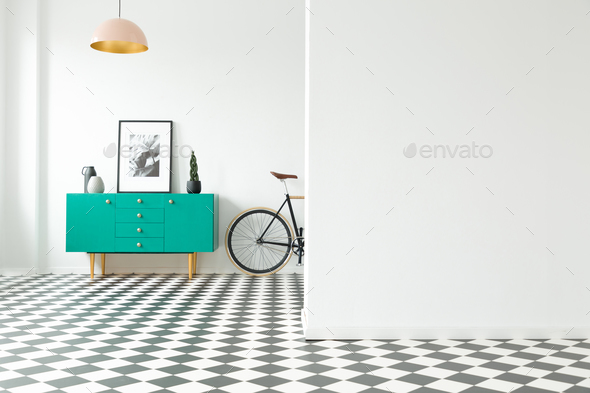 Empty wall and turquoise cabinet with decorations standing next - Stock Photo - Images