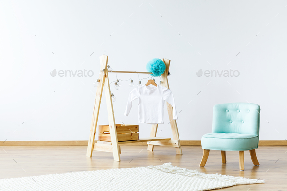 Diy hanger with a blouse, lights and box standing next to a blue - Stock Photo - Images