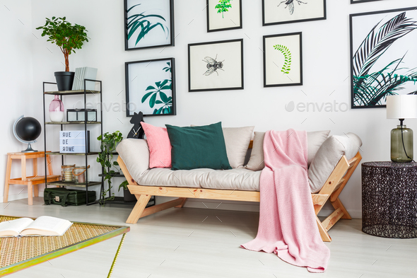 Real photo of a sofa standing next to a wall with paintings and - Stock Photo - Images