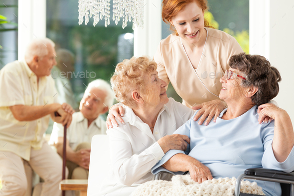 Happy friendship in old age. Tender caregiver standing behind se - Stock Photo - Images