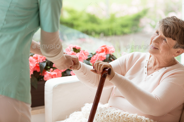 Doctor helping an elderly woman with Parkinson's disease get up - Stock Photo - Images