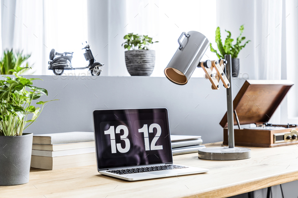 Close-up photo of laptop with clock screensaver placed on wooden - Stock Photo - Images