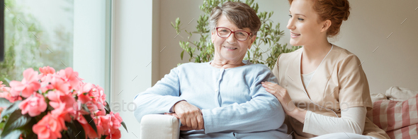 Professional caretaker with her senior charge sitting on a sofa - Stock Photo - Images